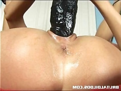 Gorgeous dark haired European babe fills her pussy and ass with a giant dildo