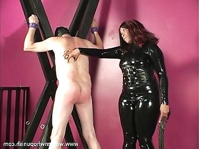 Black domina spanks and whips suspended male slave